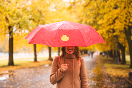 Happy woman with red umbrella walking at the rain in beautiful autumn park Stock Photo