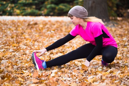 Young sport woman doing exercises during autumn training outside