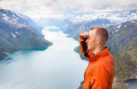 Sport couple hiking on Besseggen. Hikers enjoy beautiful lake and good weather in Norway.
