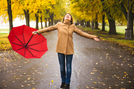 Happy woman with red umbrella walking at the rain in beautiful autumn park.