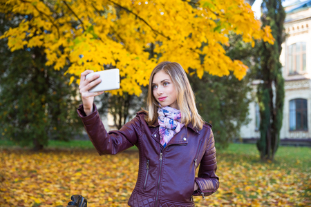 Happy teen girl with phone smile during walking on autumn park. Fall concept