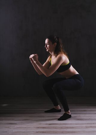 Fitness woman training in dark studio. Young girl posing on black background