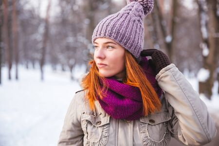 Happy redhead woman walking in winter park and enjoy the snow Standard-Bild