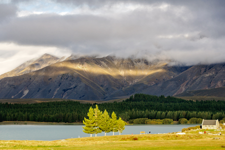 Sun breaking through the clouds over Lake Tekapo and the Church of the Good Sheppard on the South Island of New Zealand Stock Photo