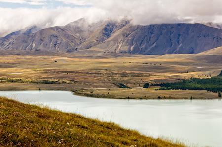 Lake Tekapo and the surrounding hills under clouds - South Island, New Zealand Stock Photo