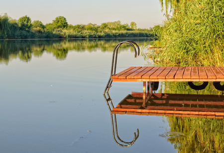 Pier and its image in the scenic Holt-Koros River at Bekesszentandras, Hungary