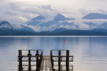 anau: Pier on, mountains behind and clouds above  Lake Te Anau in the Fiordland National Park on the South Island of New Zealand