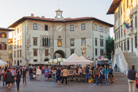 Locals and tourists visit the small bazar in front of Palazzo dellOrologio on Knights Square (Piazza dei Cavalieri), the second main square of Pisa in Tuscany, Italy - 8 October 2011