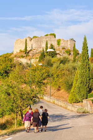 Senhoras idosas caminhar juntos para casa ao pé do Castelo de Rocca Tentennano em Castiglione d'Orcia, Toscana, Itália - 22 de setembro de 2011 Foto de archivo - 78555219