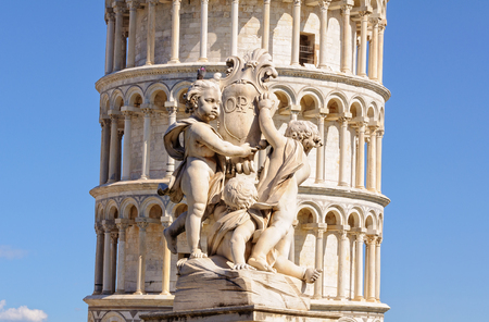 A pigeon sitting on the head of one of the opa cherubs in front of the Leaning Tower in Pisa, Tuscany, Italy Stock Photo