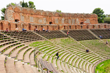 Tourists sit on the grandstand and admire the remnants of the ancient Greek theatre - Taormina, Sicily, Italy, 22 October 2011