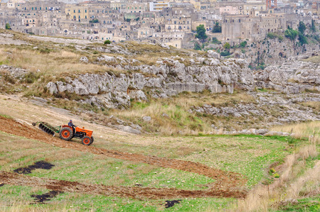 A farmer is ploughing his field just a stones throw away from Sasso Caveoso, the startling cave town - Matera, Basilicata, Italy, 26 October 2011