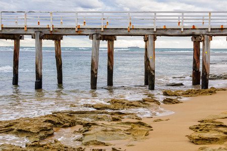 lonsdale: Old pillars of the Point Lonsdale Pier with a container ship on the horizon - Victoria, Australia Stock Photo