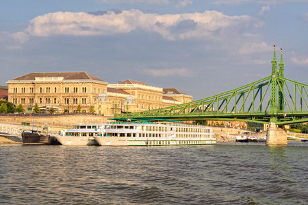 Danube river cruise ships at the Liberty Bridge and Corvinus University of Budapest, Hungary