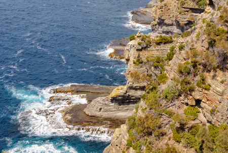 Slowly but steadily waves weather and erode the rocks under the Devil's Kitchen Lookout - Eaglehawk Neck, Tasmania, Australia