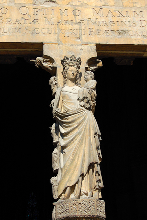 The statue of Virgin Mary with the Child in the central portal of the West facade of the Cathedral of Notre-Dame at Reims, France Stock Photo