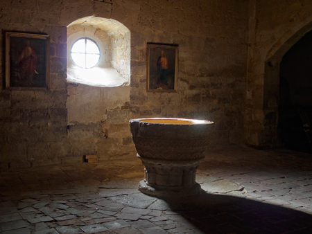 14th century stone baptismal font in the Church of Santa Maria - Boadilla del Camino, Castile and Leon, Spain