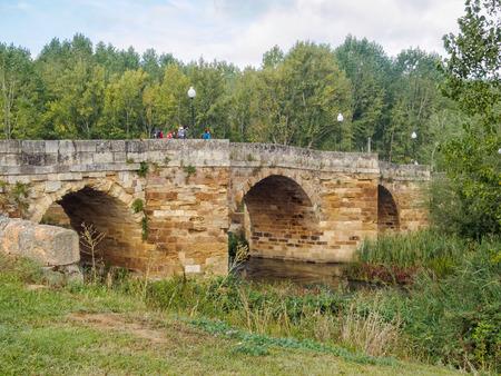 Camino pilgrims walk on the Singing Bridge (Puente Canto), an 11th century stone arched bridge, over the Cea River - Sahagun, Castile and Leon, Spain, 18 September Editorial