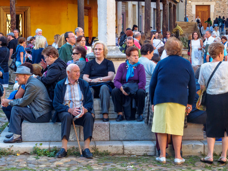 Elderly locals get together and have some rest on the steps of the stone cross on the Santa Maria del Camino Square (Plaza), also known as Grain square - Leon, Castile and Leon, Spain, 20 September 2014 Editöryel