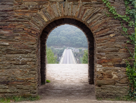 The new bridge over the Minho River as seen through an ancient surviving archway in a foggy autumn morning - Portomarin, Galicia, Spain Stock Photo