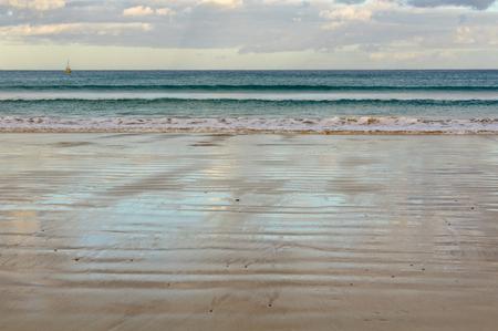 Gentle waves wash the main beach at low tide - Apollo Bay, Victoria, Australia Archivio Fotografico - 125675695