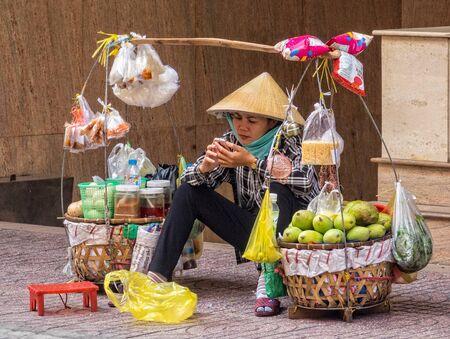 A street vendor checking her mobile phone - Ho Chi Minh City, Vietnam