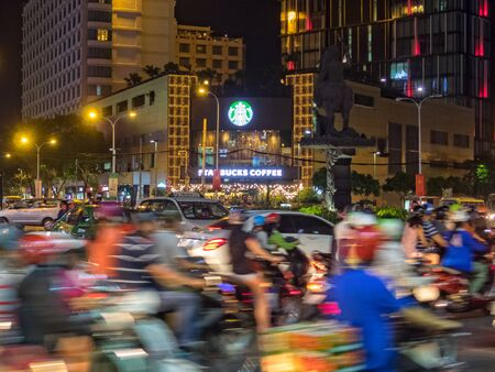 Heavy traffic at night in front of the AB Tower Starbucks Coffee - Ho Chi Minh City, Vietnam