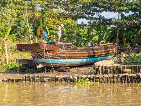 Traditional Mekong Delta freight boat under repair - Vinh Long, Vietnam
