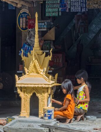 Children paint a yellow pagoda in preparation for the Vietnamese New Year - Tra Vinh, Vietnam