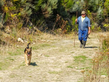 A man and his dog are walking home on a dirt road up in the mountains - San Fiz de Seo, Castile and Leon, Spain