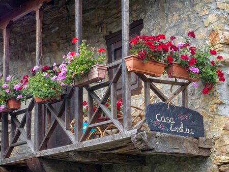 The balcony of Casa Emilia is decorated by blooming geranium - Vilasinde, Castile and Leon, Spain