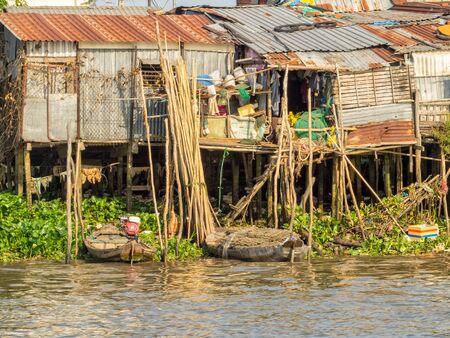 Shacks on stilts alog the Hau River in the Mekong Delta - Can Tho, Vietnam