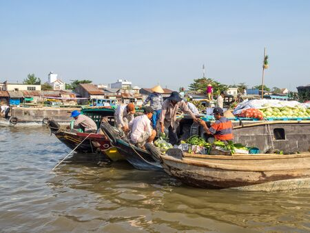 Locals are trading goods from their boats in the floating market on the Mekong River Delta - Cai Rang, Vietnam