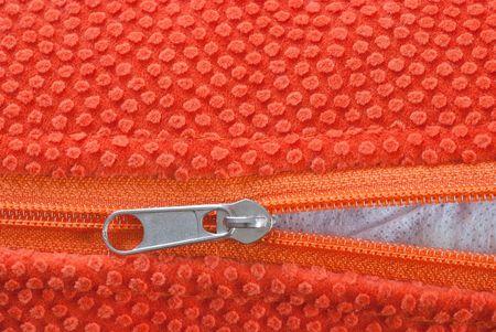 unclosed: studio shot of orange zipper, halfway open.