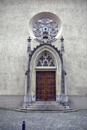 brown door stairs and church in felkierk austria