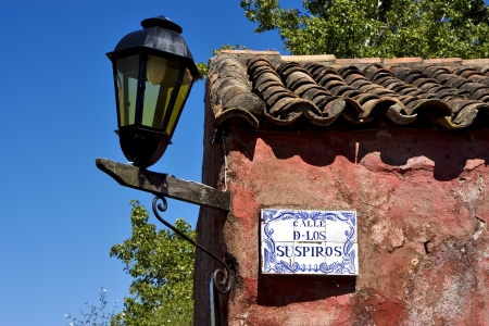 a street lamp plate plant and a wall in calle de los suspiros of house in colonia del sacramento  uruguay photo