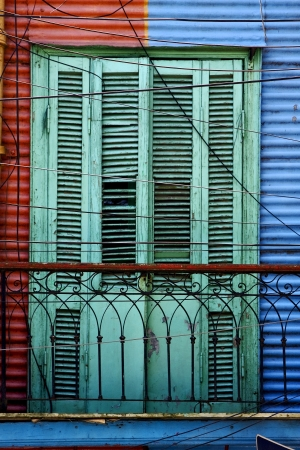 la boca: green wood venetian blind and a red blue metal wall in la boca buenos aires argentina