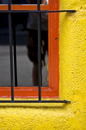 old red window and iron grate in a yellow wall in the centre of buenos aires argentina Stock Photo - 17711491