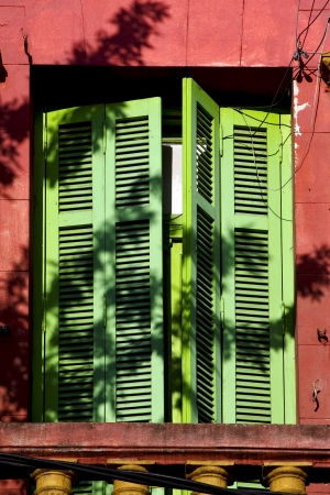 old  yellow little terrace green venetian blind and roof  in the centre of buenos aires la boca argentina photo