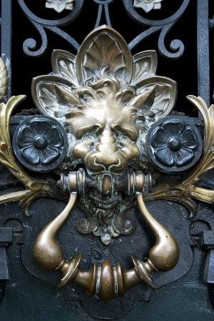 brass brown knocker in a closed green wood  door buenos aires argentina  photo