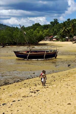 boat sand lagoon house child and coastline in madagascar nosy be Stock Photo