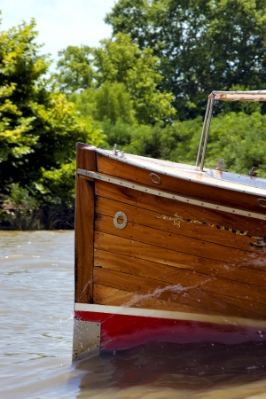 tigre: red prow boat water and coastline in rio de la plata el tigre buenos aires argentina  Stock Photo