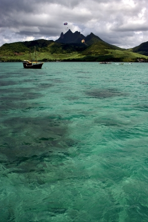 tropical lagoon hill navigable  froth cloudy  pirate boat  and coastline in Deer Island mauritius photo