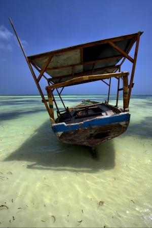 boat beach rope sand and sea in zanzibar coastline photo