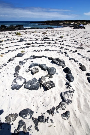 spiral of black rocks in the white  beach  in lanzarote spain photo