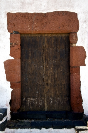 canarias: brass brown knocker in a brown closed wood  door and white wall lanzarote abstract  spain canarias