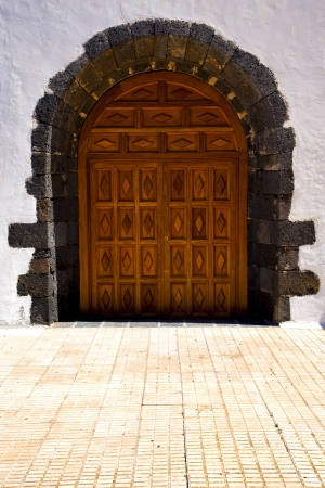 brass brown knocker in a brown closed wood  church door and white wall lanzarote abstract  spain canarias  photo