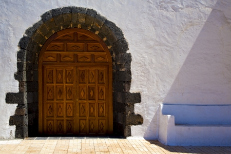 canarias: brass brown knocker in a brown closed wood  church door and white wall lanzarote abstract  spain canarias  Stock Photo