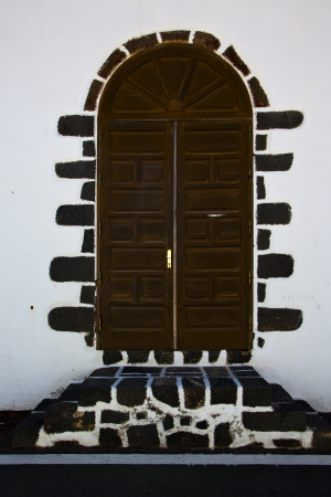 brass brown knocker in a brown closed wood  door and white wall lanzarote abstract  spain canarias  photo