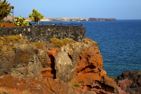 street lamp bush  rock stone sky  water  coastline and summer in el golfo lanzarote spain  photo